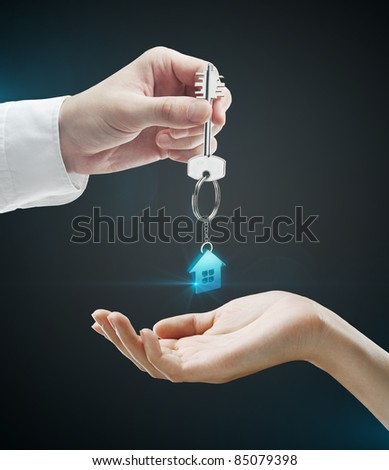 Man is handing a house key to a woman.Key with a keychain in the shape of the house. On a black background - stock photo