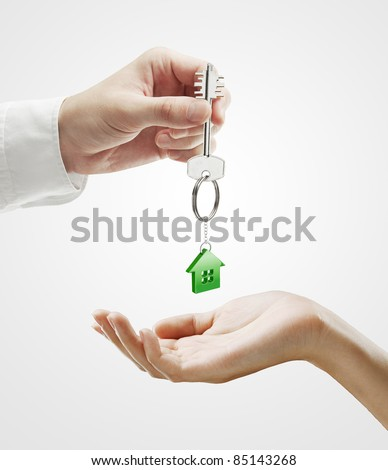 Man is handing a house key to a woman.Key with a keychain in the shape of the house. On a gray background