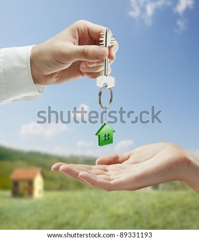 Man is handing a house key to a woman.Key with a keychain in the shape of the house. On background of nature - stock photo