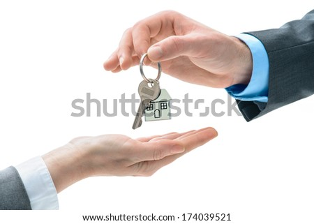Man is handing a house key to other hands. Concept of real estate and deal - stock photo