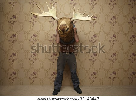 man is hiding behinde a moose head - stock photo