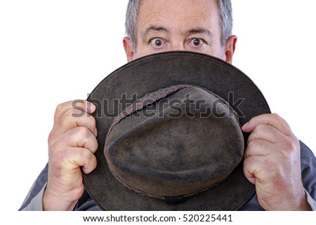 Man is holding a hat in front of his face
