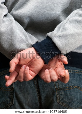 Man is holding crossed fingers behind his back... - stock photo