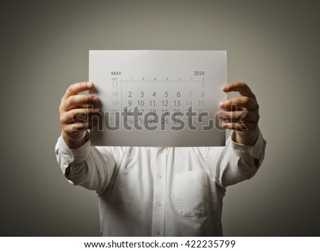Man is holding May calendar of the year two thousand sixteen.