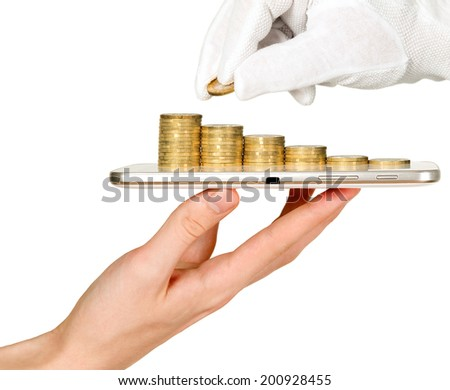 Man is holding mobile phone and showing tower of coins - stock photo