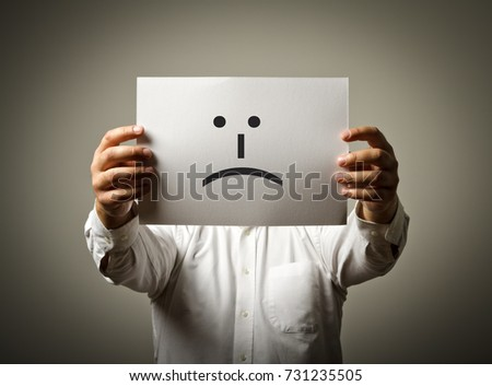 Man is holding white paper with smile. Unhappy and trouble concept.