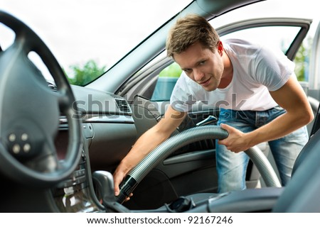 Man is hoovering or cleaning the car - stock photo