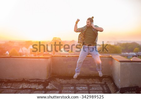 Man is jumping in the air on the top of the building using his smart phone. Shallow depth of field. - stock photo