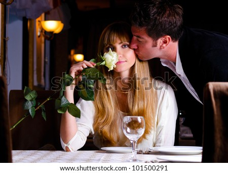 man is kissing woman sitting at restaurant - stock photo