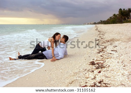 man is laying on beach as woman crawls out of the water on top of him - stock photo