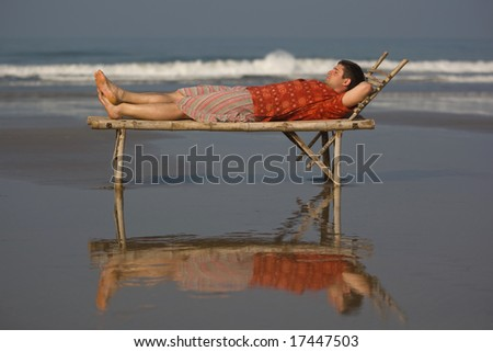 man is lieing on the trestle-bed - stock photo