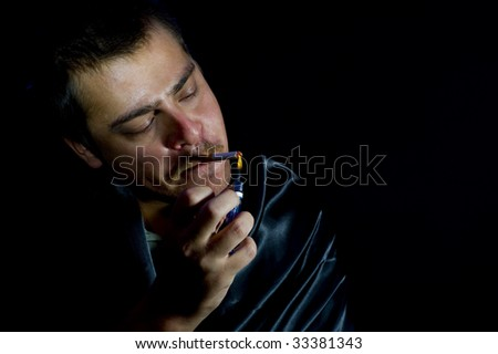 man is lighting a cigarette - stock photo