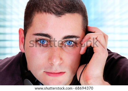 Man is listening to the music  on light blue background - stock photo