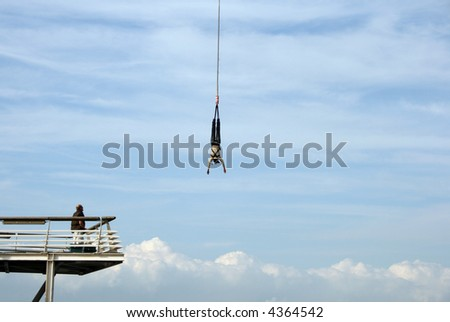 Man is looking at a bungy jumping girl - stock photo