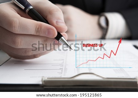 man is looking for information in the in the budget figures close-up - stock photo