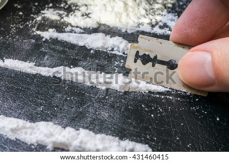 Man is making lines of cocaine white powder for snorting. - stock photo