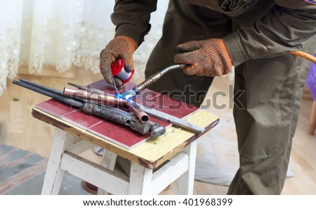 Man is making seam with gas soldering iron on copper pipe - stock photo