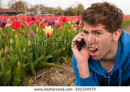Man is making terrible phone call in the flower fields - stock photo