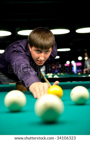 Man is playing billiard. Focus point on the face. - stock photo