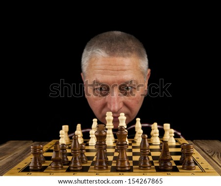 man is playing chess on a black background - stock photo