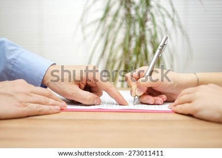 man is pointing a place where she should sign the agreement - stock photo