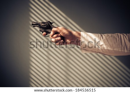 Man is pointing a revolver at a window with shadows from the blinds - stock photo