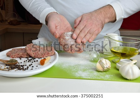 Man is preparing hamburgers in home kitchen - stock photo