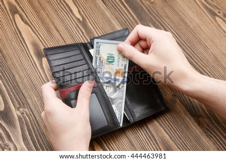 man is putting 100 dollar banknote in a black leather wallet over dark wooden background. Close up shot of hands and wallet