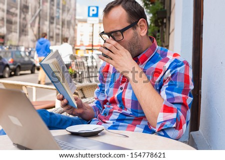Man is reading a book in cafe. He is drinking coffee. - stock photo