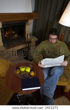 Man is reading the newspaper in front of the fireplace and enjoys the comfort of his home. - stock photo