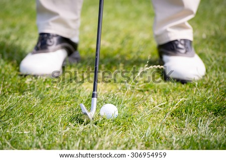 Man is ready to hit the golf ball on the grass with his golf club. Wearing white shoes. The grass is high. - stock photo