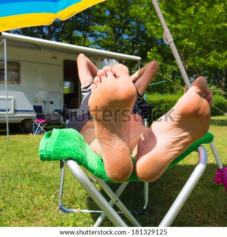 Man is resting in the sun at his mobil home - stock photo