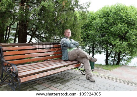 Man is resting on a wooden bench in a park