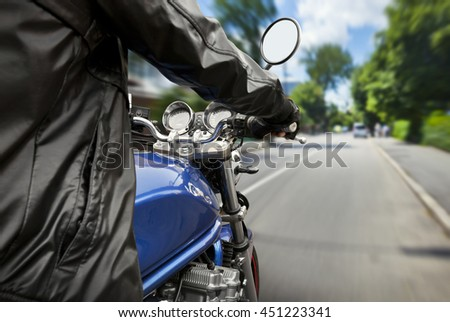 Man is riding a motorcycle on big speed by the asphalt road - stock photo