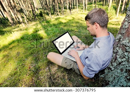 man is sitting against a tree in the forest, working with his laptop - stock photo