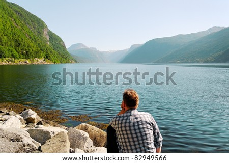 Man is sitting at the Norway fjord. - stock photo