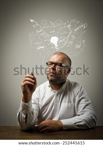 Man is sitting at the table and is ready to write something. Man in white is full of ideas. Concept of ideas and fantasy. - stock photo