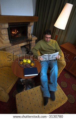 Man is sitting in the armchair at home in front of the fireplace. He is reading the newspaper. - stock photo