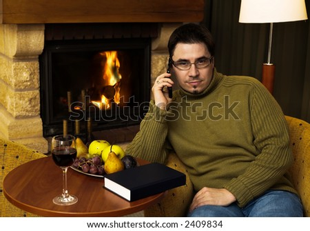 Man is sitting in the armchair at home in front of the fireplace. He talks on a cell phone and looks at the camera. - stock photo