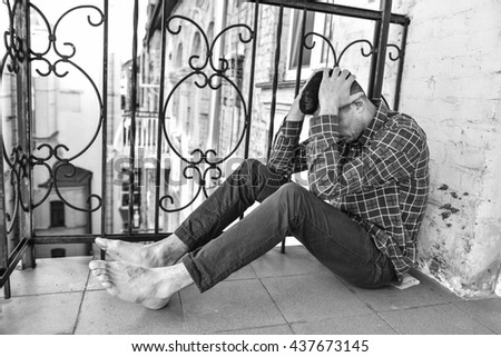 Man is sitting on the balcony. Person feels terrible emotional pain and helplessness. The addict feels bad - stock photo
