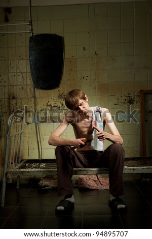 Man is sitting on the metal bed and examine the blade of his axe