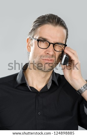 man is skeptical on the phone - stock photo