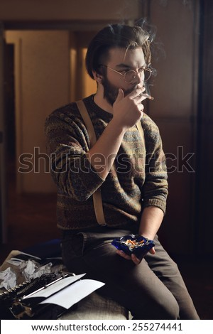 man is smoking cigarette at a table with a typewriter - stock photo