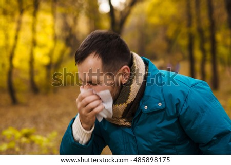 Man is sneezing  in the autumn park