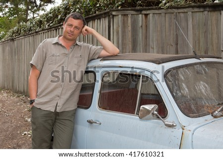 Man is standing near a vintage car on the beach