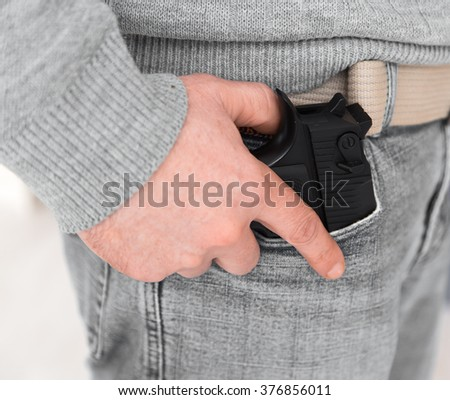 man is standing with his gun in his hand. Man holding a gun.