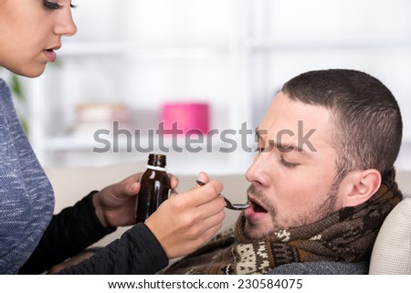Man is suffering from a cold. Woman gives him medicine. - stock photo