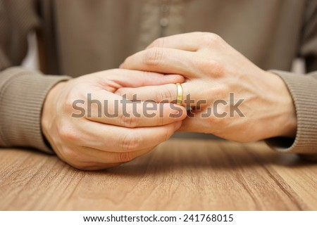 Man is taking off the wedding ring - stock photo