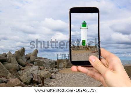 Man is taking photo of green lighthouse with smart mobile phone - stock photo