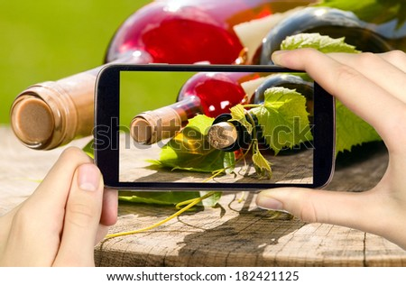 Man is taking photo of wine bottles with smart mobile phone - stock photo